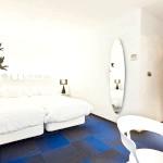 Спальня в білому з синім килимом