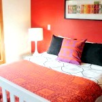 Червоно-біла спальня з чорними аксесуарами.